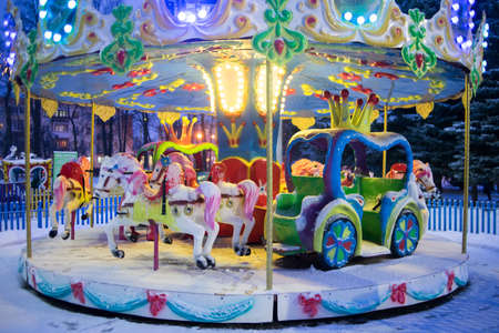 Childrens carousel glows beautifully in winter. Attraction for children Archivio Fotografico