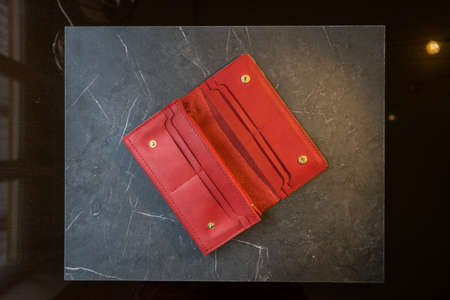 U-turn red handmade leather wallet. leather purse on a beautiful dark background