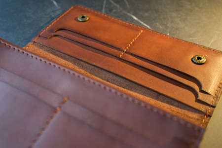 U-turn brown handmade leather wallet. Brown leather purse on a dark background