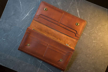 U-turn brown handmade leather wallet. leather purse on a dark background