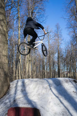 bmx rider does a dirt jumping trick in the winter. Moto whip on bmx 스톡 콘텐츠 - 150903200