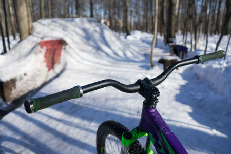 the bike stands in the background of dirt jumping in winter. High quality photo 스톡 콘텐츠