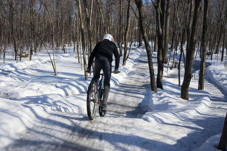 rider rides on a pump track in winter. The cyclist accelerates to jump on dirt jumping. slippery pump track in winter in snow. High quality photo