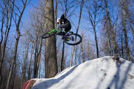 A cyclist does a 360 trick on a springboard in winter. Athlete shows a trick Banco de Imagens - 150903510