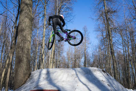 Mountain biker rider does a dirt jumping trick in the winter. Moto whip on bike Banco de Imagens - 150903201