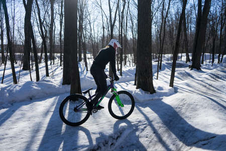 A man rides a bicycle on a pump-track in the winter in a helmet. 스톡 콘텐츠