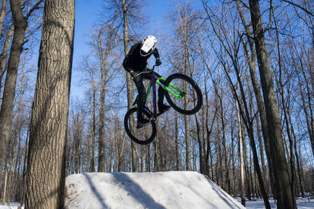 mtb rider does trick on dirt jumping in winter. Cyclist doing springboard stunt Stock Photo