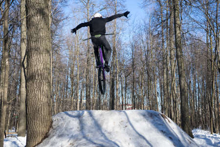 Athlete does a nohand trick on a bicycle. Winter dirt jumping Banco de Imagens - 150903391