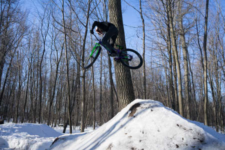 A cyclist does a 360 trick on a springboard in winter. Athlete shows a trick Banco de Imagens - 150903650