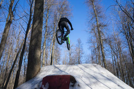 guy jumps on a springboard on a bicycle in winter. winter dirt jumping