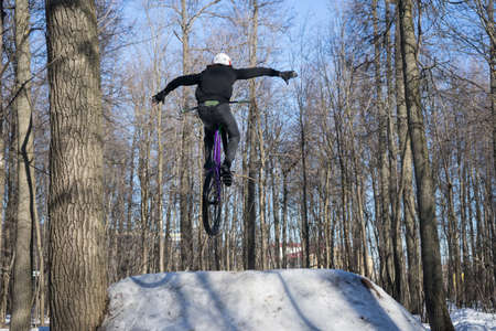 Athlete does a nohand trick on a bicycle. Winter dirt jumping Banco de Imagens - 150904506