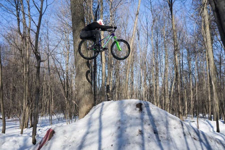 Rider jumps on a bicycle in winter dirt jumping. Cyclist doing a trick Stock Photo