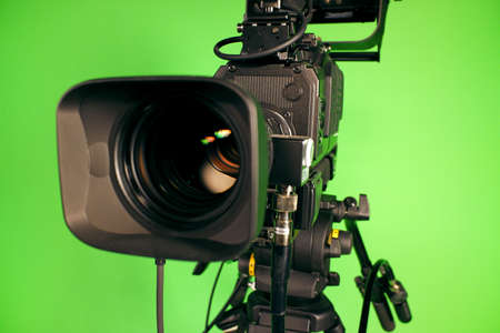TV video camera on the background of a green chroma key. Camcorder lens