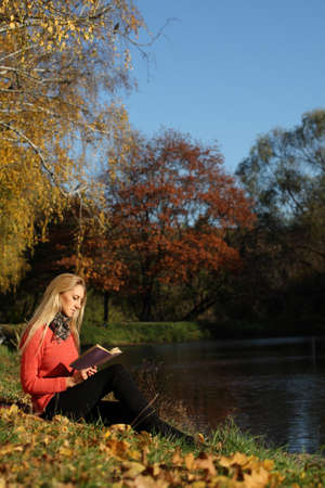girl reading in autumn park photo
