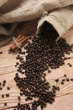 opened bag: Coffee beans in coffee sack made from burlap on wooden surface