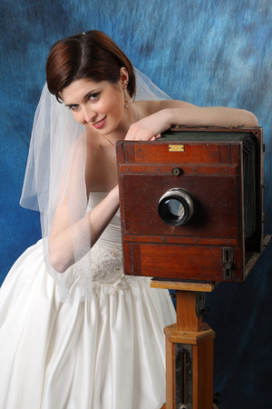 charming bride with an old camera on a blue background photo