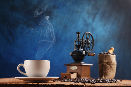 cup of coffee, coffee grinder, coffee beans in a sack on a wooden background photo