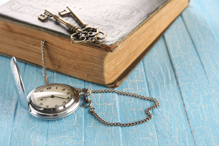 Vintage pocket watch, old book and a brass key on painted blue boards photo