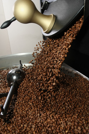 Freshly roasted coffee beans spilled out coffee roasting machines Imagens