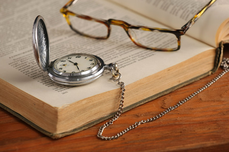 Vintage pocket watch glasses  and open old book on background of wooden planks photo