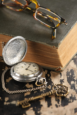 vintage pocket watch old book and Brass Key glasses photo