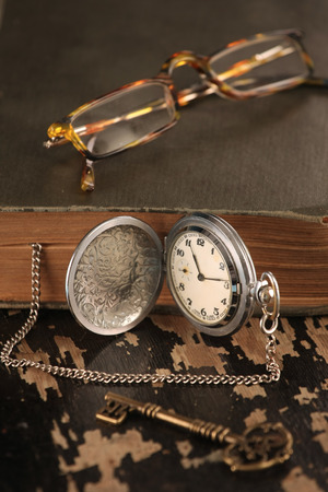 intage pocket watch old book and Brass Key glasses photo