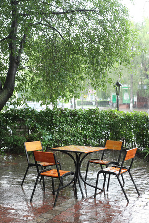 table and chairs in empty cafe in the rain photo