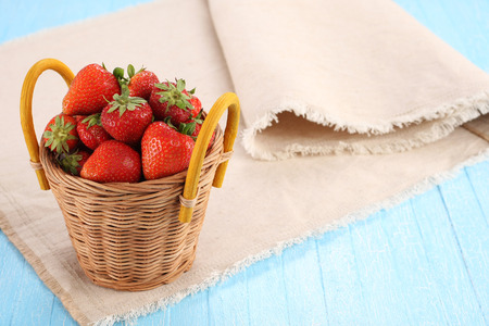 strawberries in a wicker basket on a wooden boards painted photo