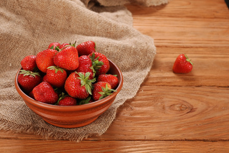 fresh strawberries in a clay bowl on burlap background and wooden planks photo