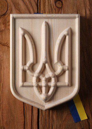 armorial: Coat of arms of Ukraine (state emblem, national ukrainian )  carved from a tree on a white background isolate Stock Photo