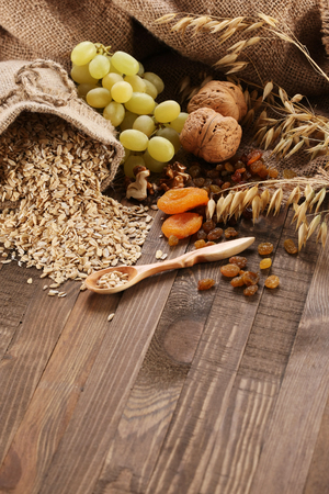 oatmeal in a sac, ears of oats, dried apricots, raisins, grapes, nuts on the background of wooden planks and sacking photo
