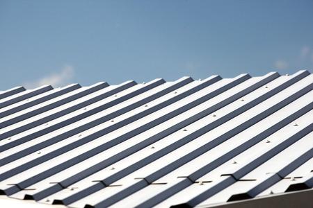 grooved: White metal hangar roof against the blue sky
