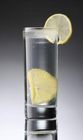 vasos de agua: Limonada en un vaso con vaso con una rodaja de limón en el fondo de la pendiente