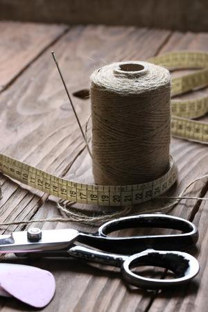 kit de costura: Tijeras y bobina de hilo de cerca sobre un fondo de tablas de madera Foto de archivo