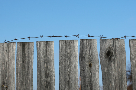 old wooden fence with barbed wire against the blue sky Stockfoto