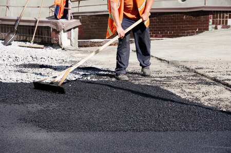 road workers level the hot asphalt by hand