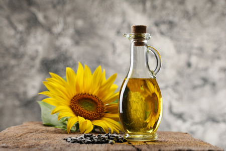 sunflower oil in a bottle, seeds and sunflower on the background of wooden boards