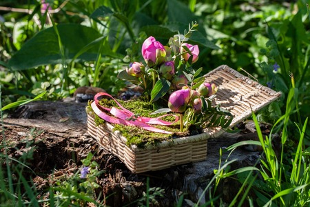 wicker box for wedding rings with beautiful flowers and natural moss Imagens