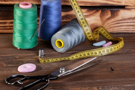 spools of thread, scissors on the background of wooden painted boards