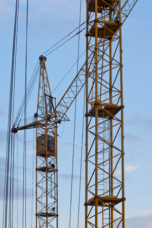 Yellow building tower crane against the blue sky. close-up Imagens