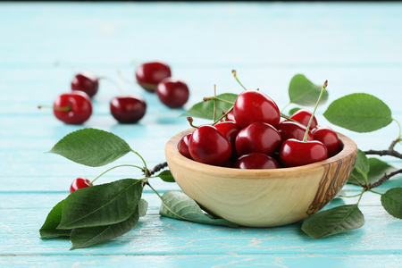 ripe cherries in a wooden bowl on the background of wooden painted boards Imagens