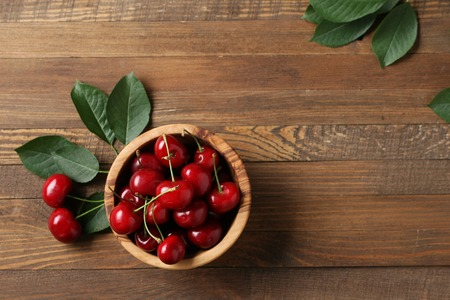 ripe cherries in a wooden bowl on the background of wooden boards Imagens