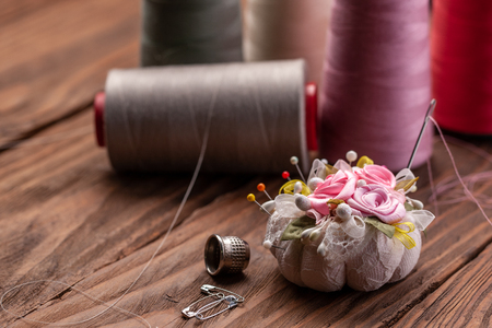 needle bed with pins, thimble and spools of thread on the background of wooden boards close-up Imagens