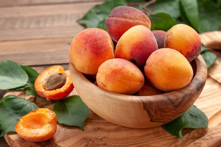 ripe apricots in a wooden bowl on the background of not painted boards close-up Stok Fotoğraf - 132113756