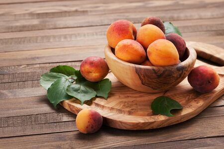 ripe apricots in a wooden bowl on the background of not painted boards close-up Stok Fotoğraf - 132113973