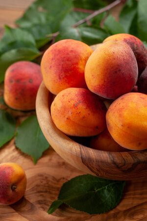 ripe apricots in a wooden bowl on the background of not painted boards close-up Stok Fotoğraf - 132113523