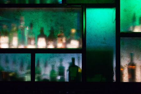 bar counter with bottles behind colored glass out of focus