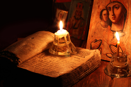 The religious book with icons and candles Stock Photo