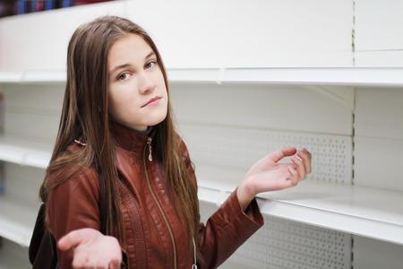 A woman standing near empty shelves