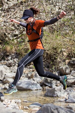 A woman in sports clothing jumping over the river gravel. National park Paklenica, the part of Velebit; the largest mountain range in Croatia.